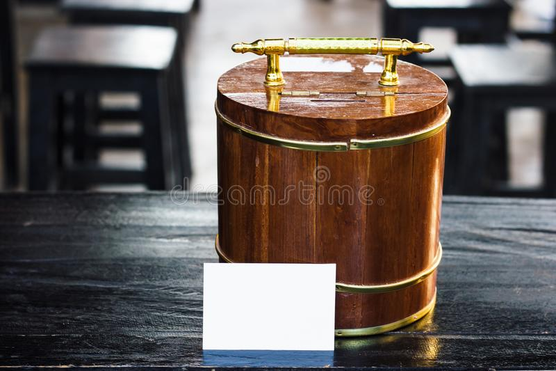 Wooden piggy bank with white paper on black wood table. Saving money concept. stock photo