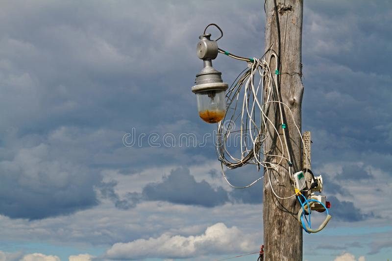 Wooden pillar with old lantern and wires against the sky stock images