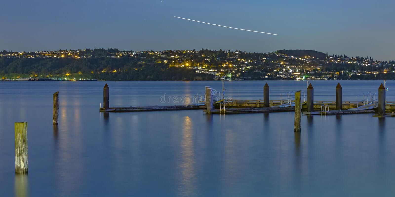 Wooden pillars in Tacoma with contrail in the sky. View of old wooden pillars and dock in Tacoma bay at sunset. A contrail from an aircraft can be seen in the royalty free stock photo
