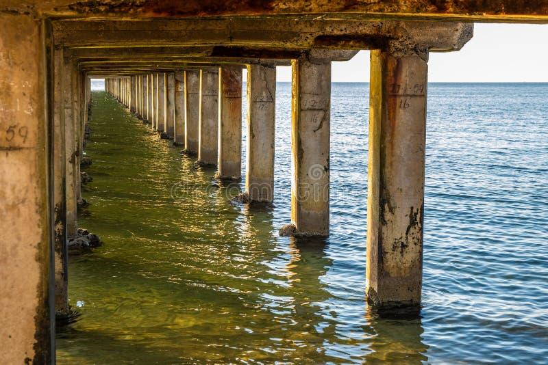 Wooden pillars underneath a pier. royalty free stock photo