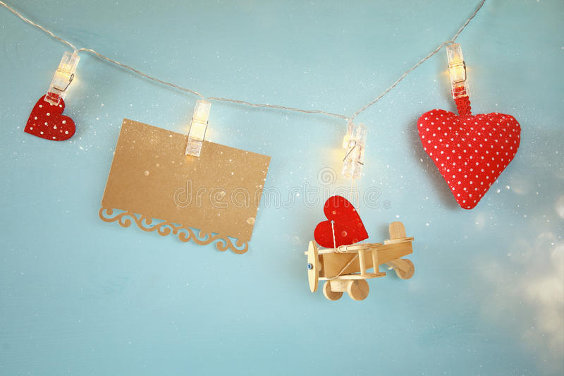 Wooden plane, hearts and empty letter hanging on garland stock image
