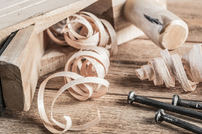 Wooden planer and filings. Old wooden jointer ruler and nails on table royalty free stock images