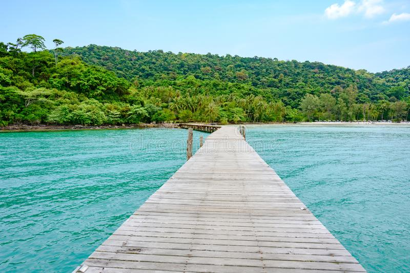 Bridge to the beach in Thailand, wooden bridge over turquoise water to beautiful thai beach with white sand and forest. Wooden planks on bridge over light green royalty free stock image
