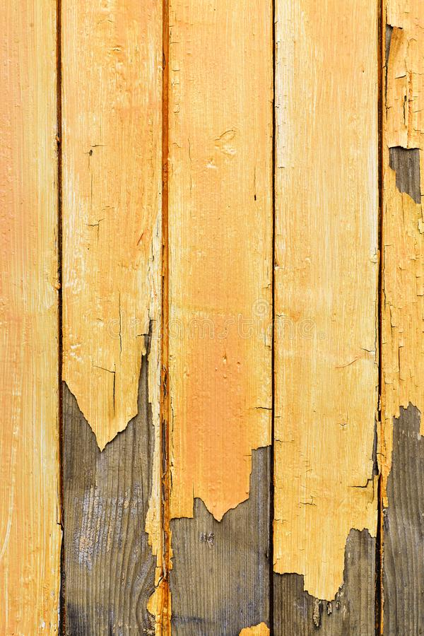 Wooden planks with peeled yellow paint, abstract texture, vertical stock photography