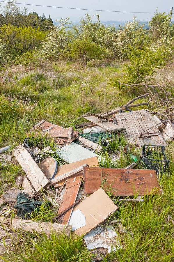 Trash let in the grass in the Italian country. Wooden and plastic garbage among the grass, in Nature, left by disrespectful people, in Italy royalty free stock images