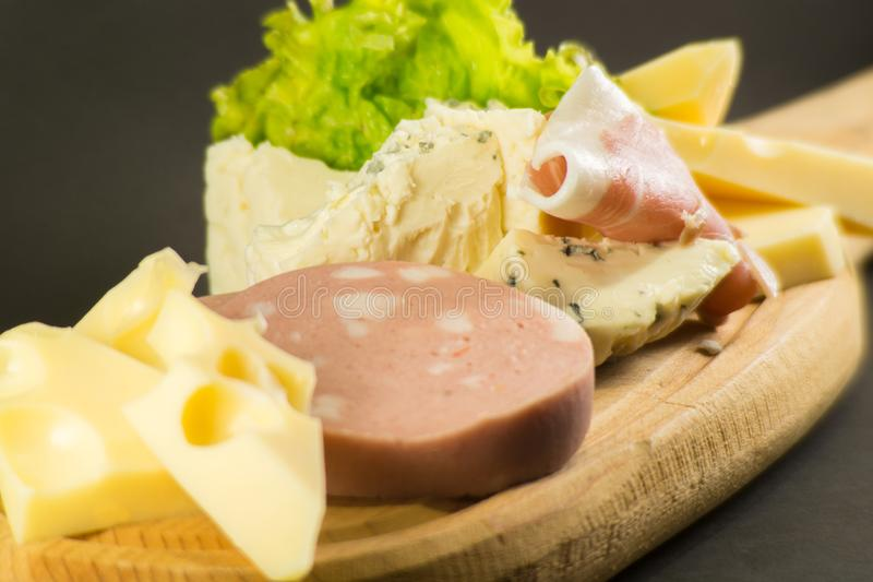 Wooden plate with cheeses and cold cuts like gruyere, mortadella, Roquefort and prosciutto. Wooden plate cheeses cold cuts like gruyere mortadella roquefort royalty free stock photo