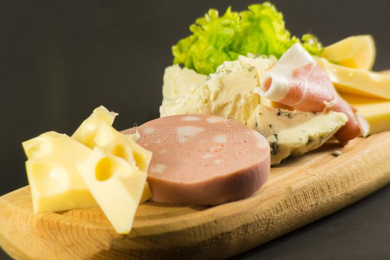 Wooden plate with cheeses and cold cuts like gruyere, mortadella, Roquefort and prosciutto. Wooden plate cheeses cold cuts like gruyere mortadella roquefort royalty free stock photography