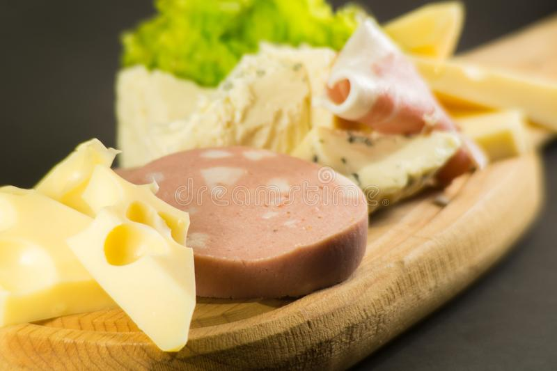 Wooden plate with cheeses and cold cuts like gruyere, mortadella, Roquefort and prosciutto. Wooden plate cheeses cold cuts like gruyere mortadella roquefort royalty free stock images