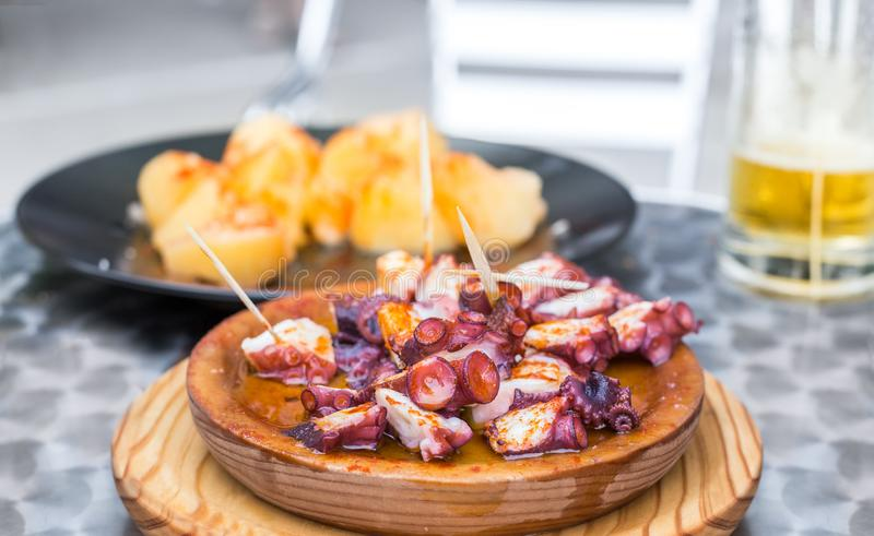 Wooden plate of galician style cooked octopus with potatoes, paprika and olive oil. Pulpo a la gallega. Wooden plate of galician style cooked octopus with royalty free stock photography
