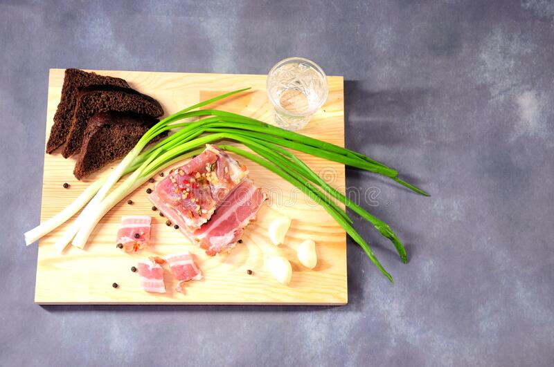 Wooden plate with a glass of cold Russian vodka, a piece of lard, green onions, garlic and slices of rye bread on a gray stock image
