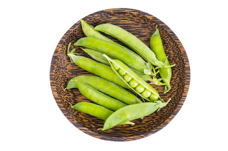 Wooden plate with green pea pods on white. Wooden plate with green pea pods. Studio Photo royalty free stock photography
