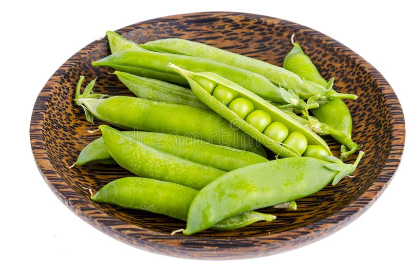 Wooden plate with green pea pods on white. Wooden plate with green pea pods. Studio Photo royalty free stock photo