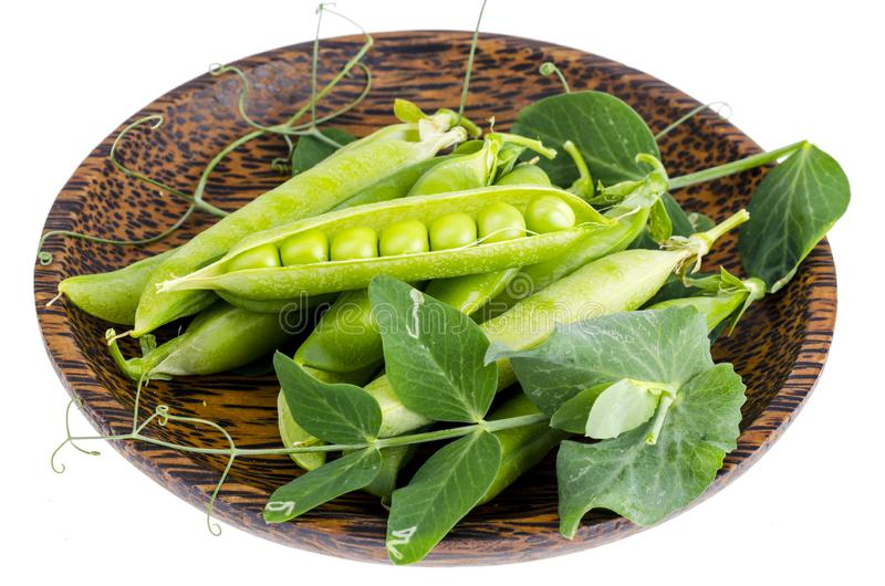 Wooden plate with green pea pods on white. Wooden plate with green pea pods. Studio Photo royalty free stock images