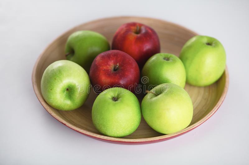 Wooden plate with ripe fresh red and green apples royalty free stock image