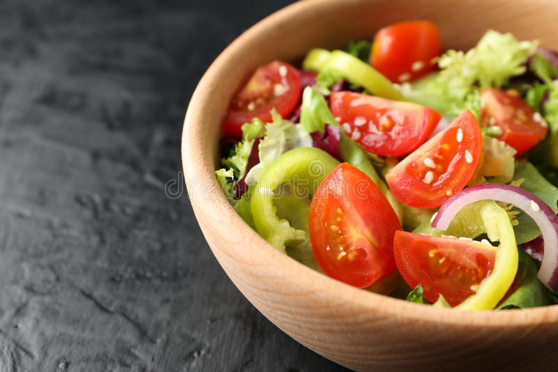 Wooden plate with salad on black background. Close up stock photo