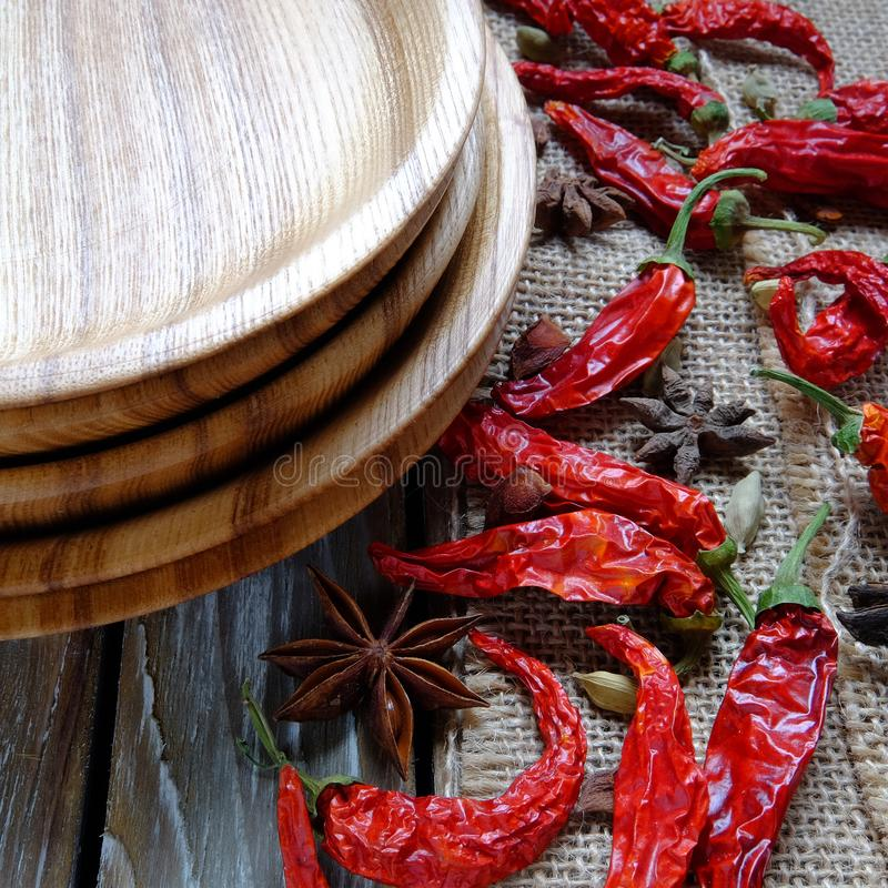 Wooden plates on a table. Wooden plates, chili pepper and spices on a vintage table royalty free stock photo