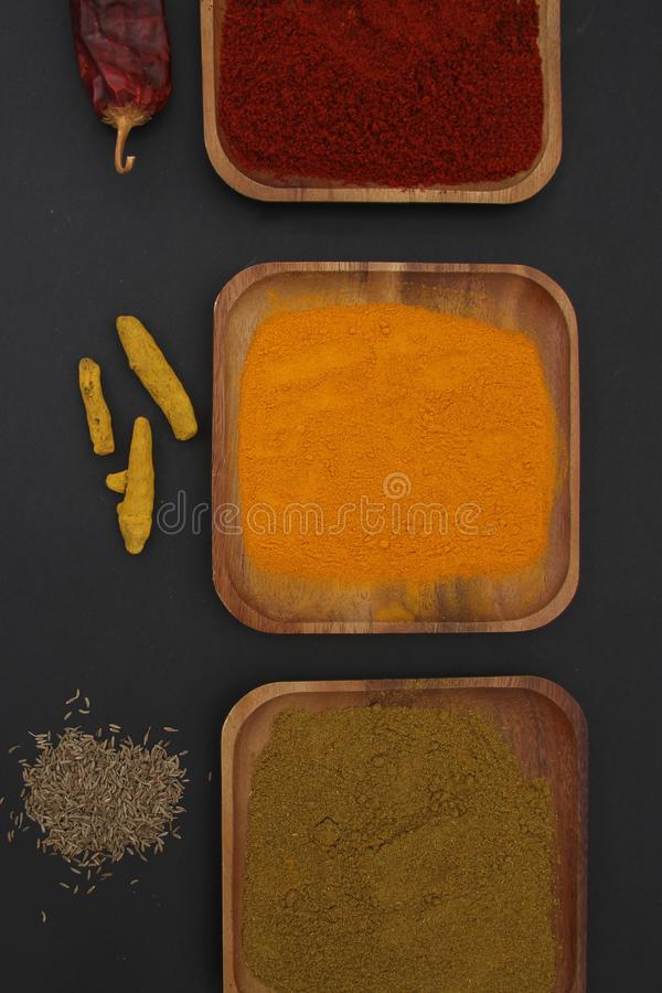 Wooden plates with spices Cumin seeds Turmeric root Dried chilli Close up stock images