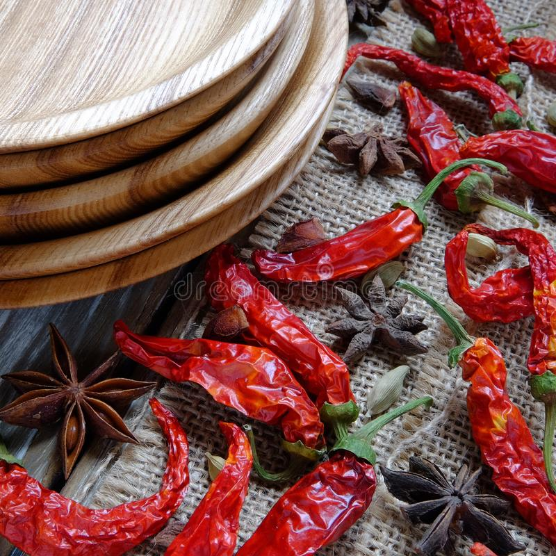 Wooden plates on a table. Wooden plates, chili pepper and spices on a vintage table stock photo