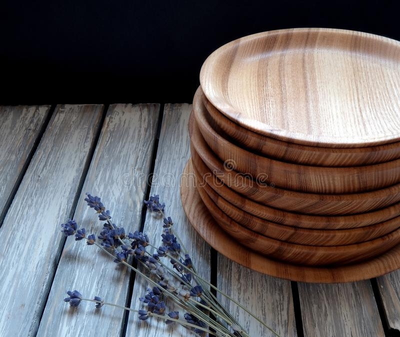 Wooden plates on a table. Wooden plates and lavender on a vintage table on a black background stock photos