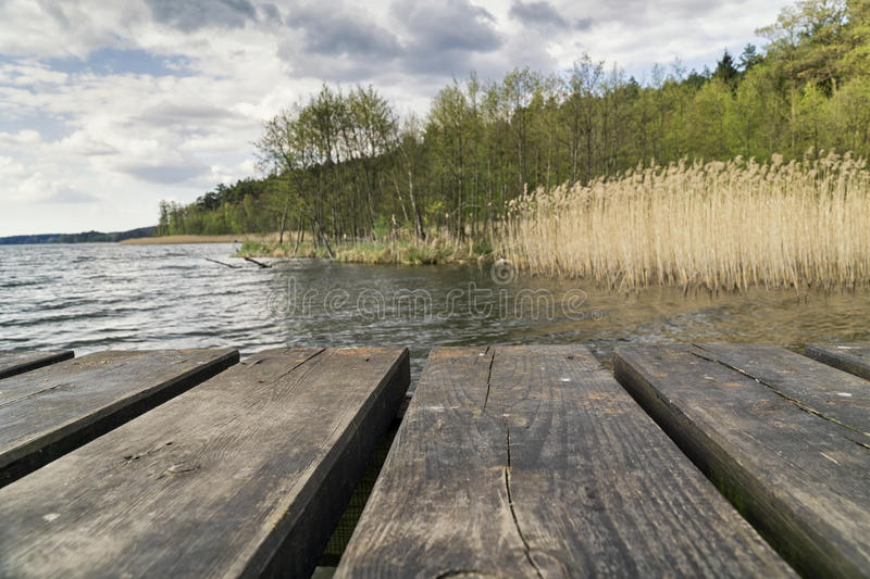 Wooden platform on the lake overlooking a shore of the lake. On a cloudy day. Real photo. Selective focus stock photo