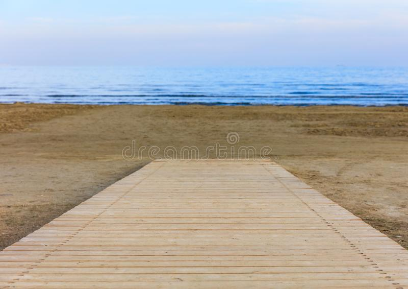 A wooden pier that leads to the sandy beach. Blurred background. A wooden platform that leads to the sandy beach. Blurred background royalty free stock image