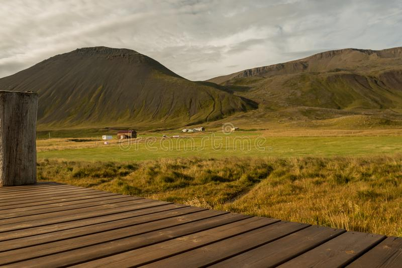 A wooden platform, a veranda overlooking the beautiful hilly mountains and valley. Spacious landscape of Iceland royalty free stock image