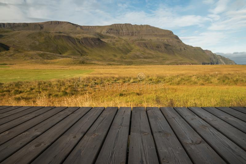 A wooden platform, a veranda overlooking the beautiful hilly mountains and valley. Spacious landscape of Iceland royalty free stock photography