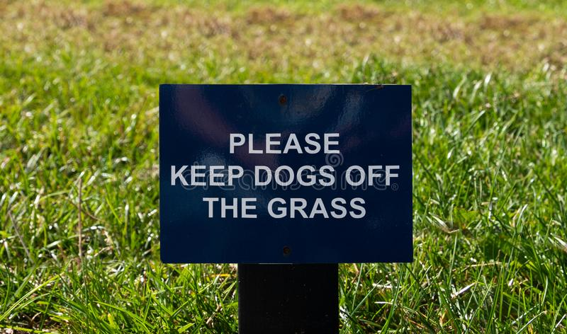 Please Keep Dogs Off The Grass sign. Wooden Please Keep Dogs Off The Grass sign by a lawn royalty free stock photography