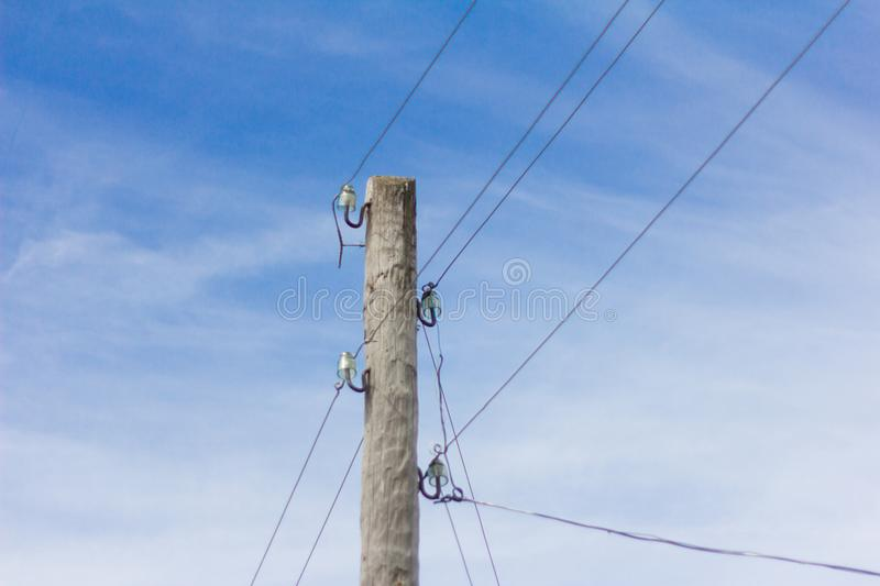 Wooden pole with electric wires on blue sky background.  royalty free stock photos