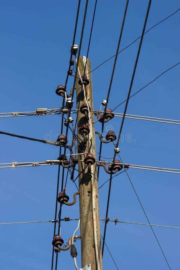 Wooden pole with electrical and telephone wires. Communication equipment and blue skies stock images