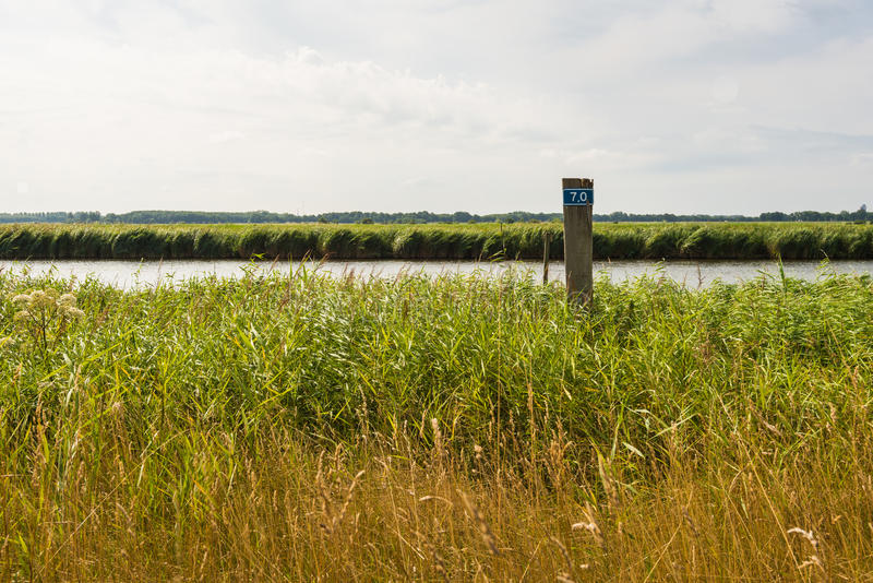 Wooden pole with a figure on the bank of a small river royalty free stock image