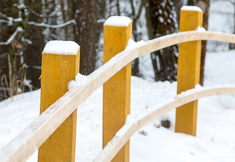 Wooden pole handrail bent beige fence winter road in the forest. yellow bars snow cap stock image