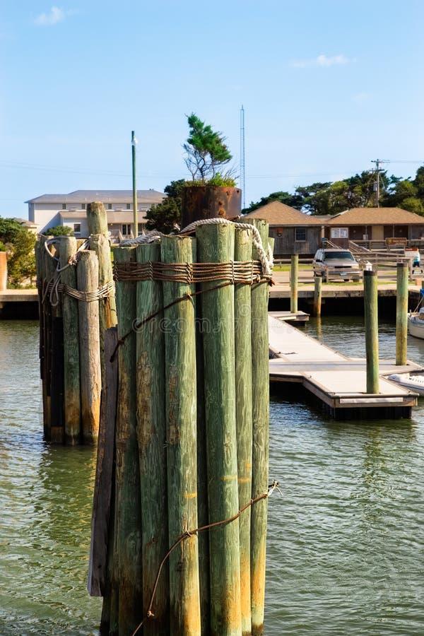 Wooden poles in Atlantic ocean. Bundle of wooden poles. Dock yard. Buffering.Pilings stock images