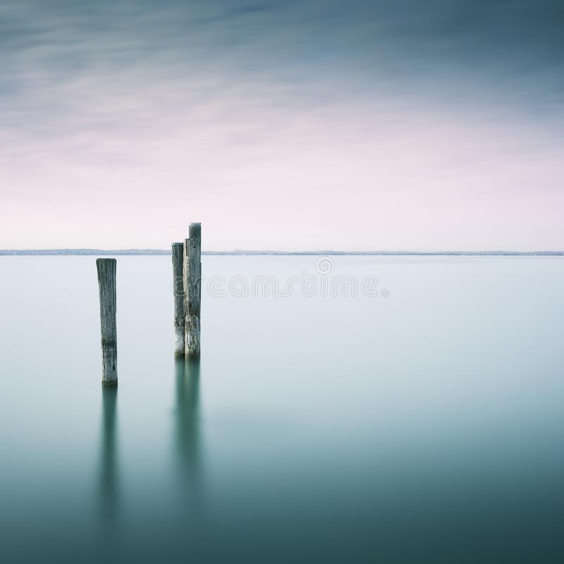 Wooden poles in a lake, long exposure time. Wooden poles in lake Gardasee in Northern Italy, Europe, long term exposure shot royalty free stock photo