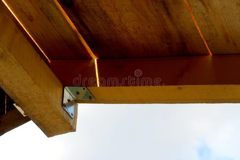 Wooden poles and roof with metal corner fixes stock images