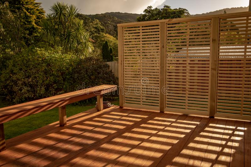 Wooden Porch With Light And Shadows From Sunset. Calm day with sunset as light begins to fade and shadows grow over garden royalty free stock photo