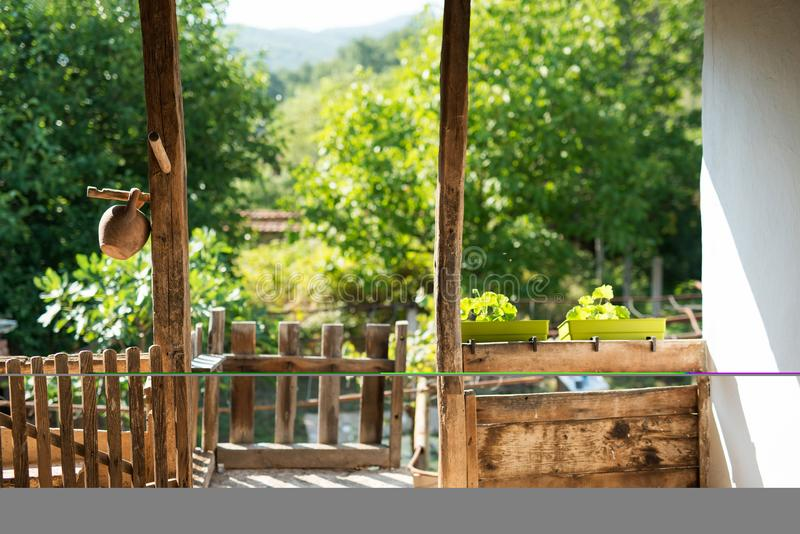 Wooden porch of an old vintage country house overlooking towards a green sunny garden in the yard royalty free stock photography