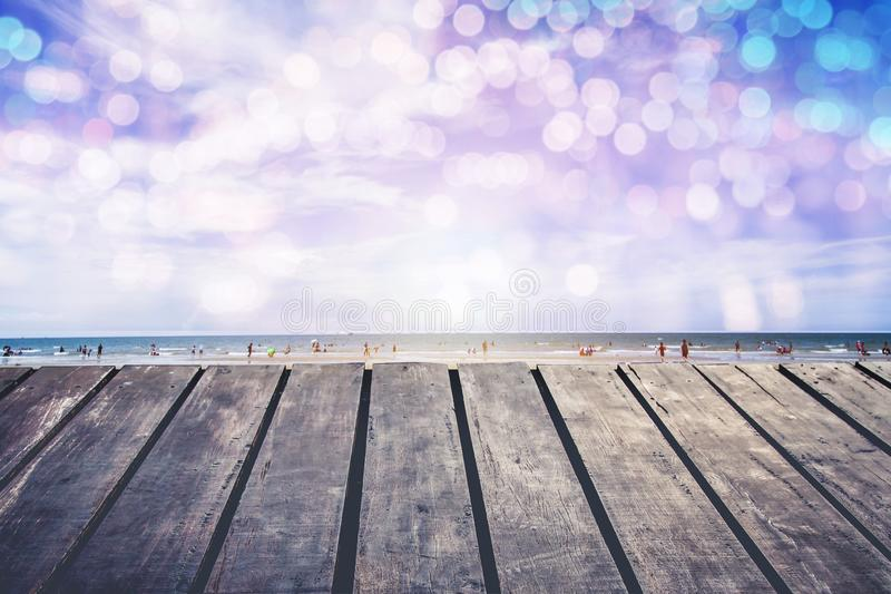 The wooden porch by the sea has bokeh lighting in the water.Enter the summer royalty free stock photography