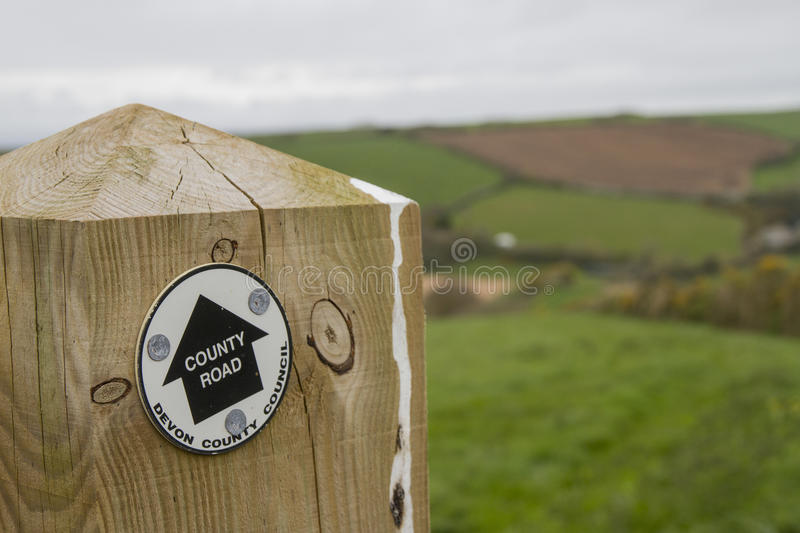 Wooden post with Devon County Road sign and green fields beyond. Bird poo on the post and green patchwork fields out of focus behind stock image