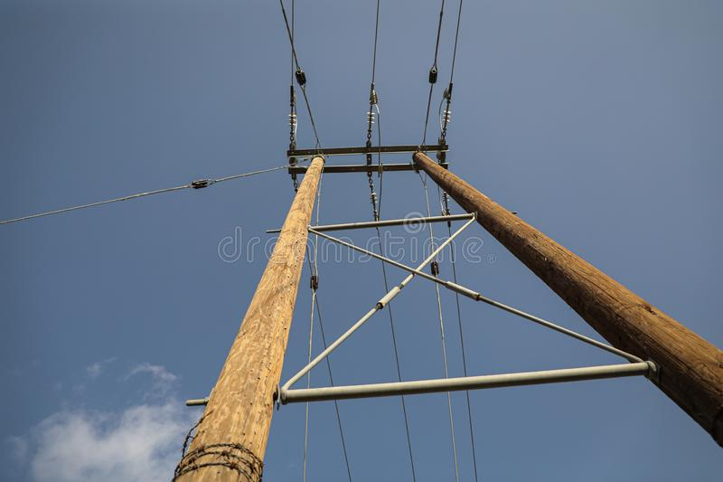 Wooden power poles with a blue sky background royalty free stock photo