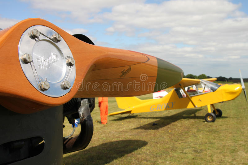 Wooden propeller and yellow high wing monoplane. Close up image of wooden propeller and yellow high wing monoplane on an airfield royalty free stock photo