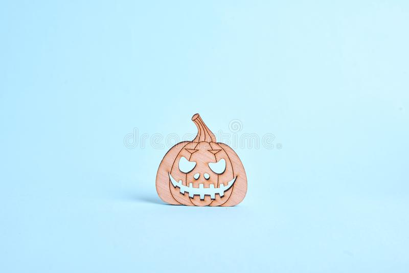 Wooden pumpkin decorative object on blue background. Halloween concept. Copy space royalty free stock photos
