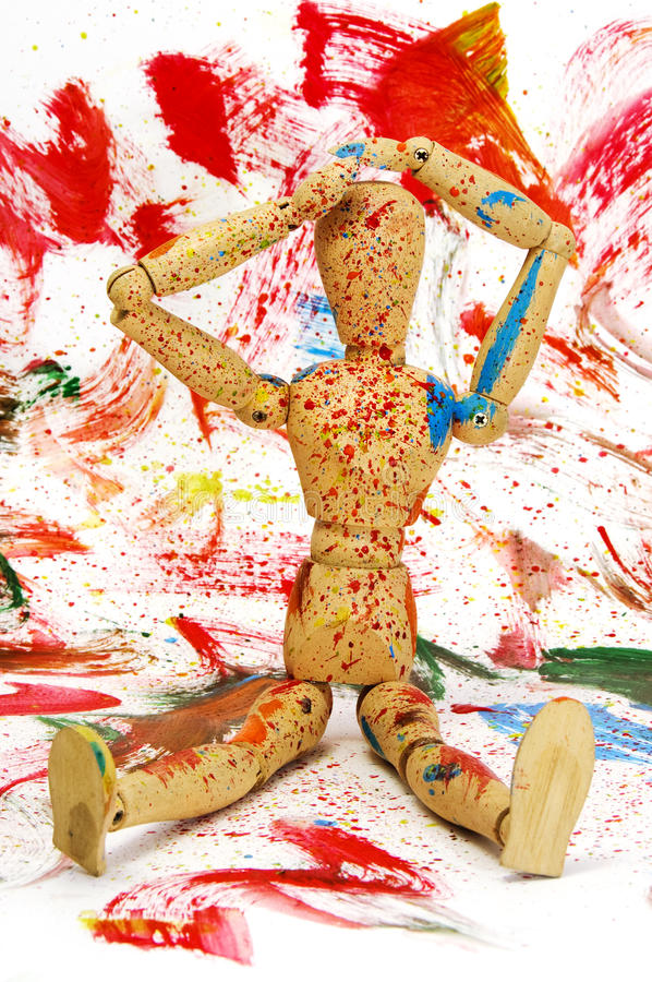 Wooden puppet. Splashed with paint of different colors on a different colors background stock photos