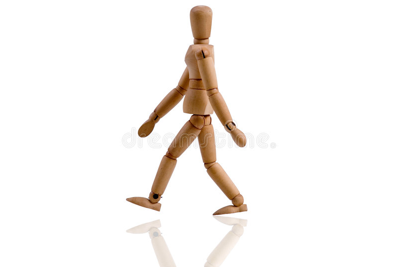 WOODEN PUPPET. A wooden puppet is walking over white stock photography