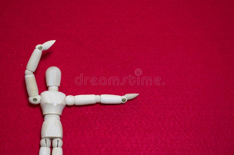 Wooden puppet on red color acrylic felt hold up arm act like present something royalty free stock image