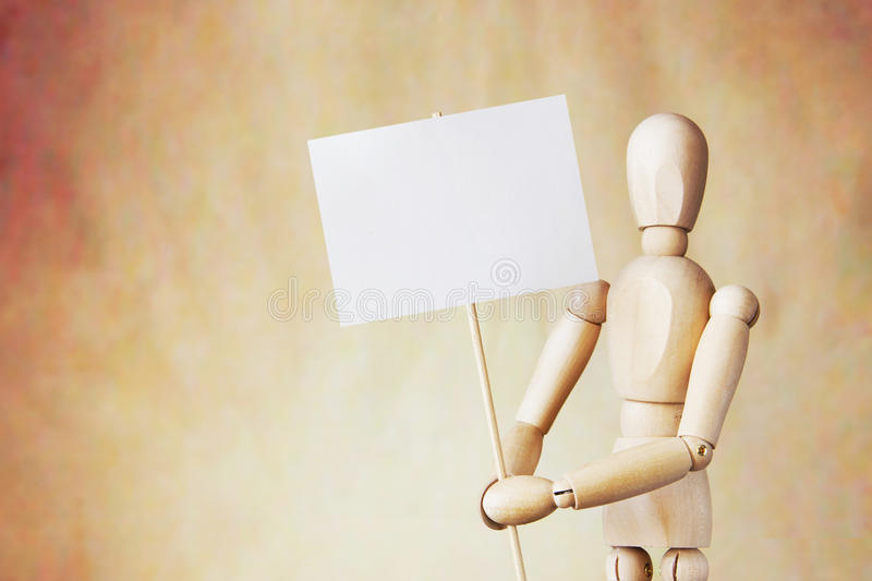 Wooden puppet holding blank white poster in its hands. Conceptual image about claims stock image