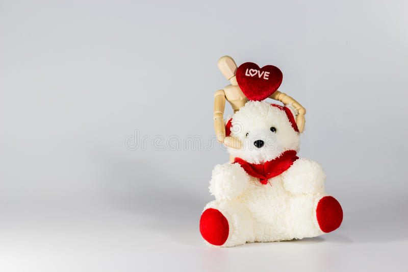 Wooden puppet. Hug red heart and teddy bear for valentine& x27;s day stock images