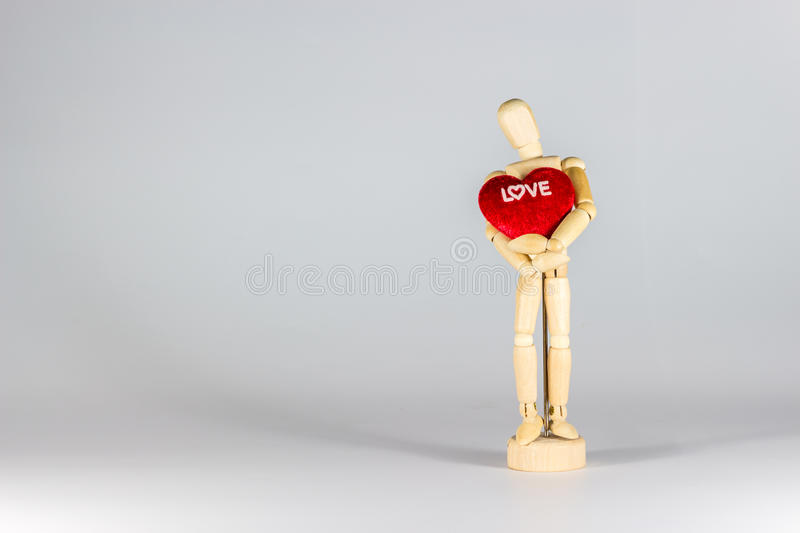 Wooden puppet. Hug red heart for valentine`s day royalty free stock image