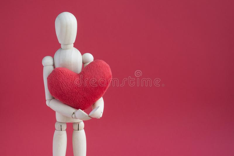 Wooden puppet human on red background holding red plush heart.  royalty free stock photos