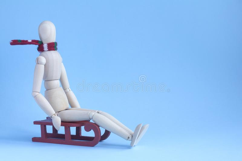 Wooden puppet human in scarf riding a red sledge.  royalty free stock photography